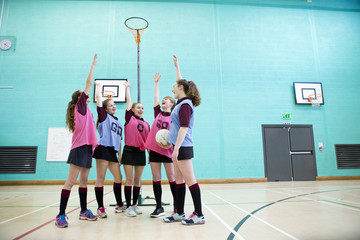 Enthusiastic high school students cheering before netball game in gym