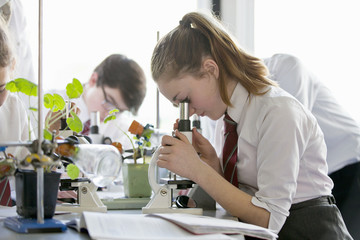 High school student conducting scientific experiment at microscope in biology class