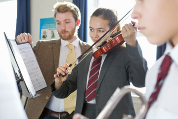 Music teacher teaching high school student playing violin in music class