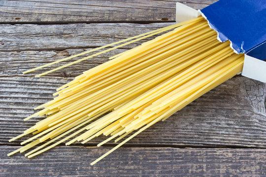 Spaghetti in cardboard box on wooden background