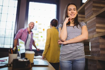 Confident businesswoman with coworkers in background