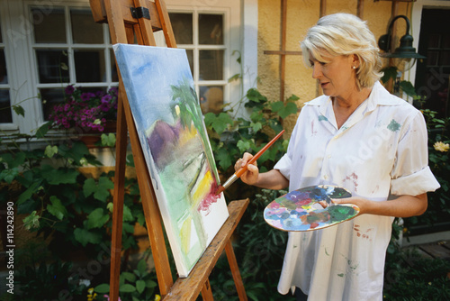 """""""Mature woman painting on an easel outdoors"""" Stock photo ..."""