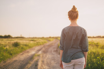 teen girl stand on rural road shot from back