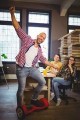 Businessman enjoying self-balanced board in creative office
