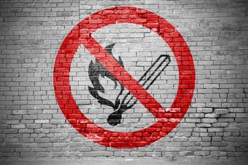 Ziegelsteinmauer mit Verbotszeichen Keine offene Flamme; Feuer, offene Zündquelle und Rauchen verboten Graffiti