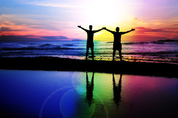 Gay couple admiring a rainbow sunset.