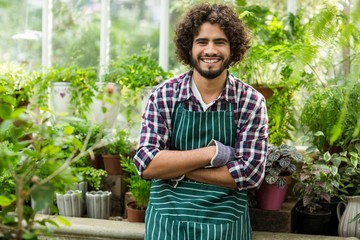 Male gardener with arms crossed at greenhouse