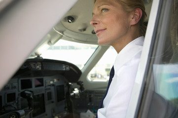 Female pilot smiling in cockpit of airplane