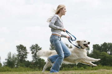Woman running with dog in park