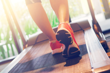 Close up on shoe athlete, Woman running in a gym on a treadmill concept for exercising and sunlight effect, fitness and healthy lifestyle