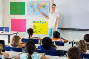 Obraz Teacher pointing on map while teaching children - fototapety do salonu