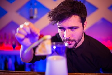 Bartender arranging fruits on cocktail glass