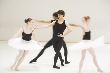 A group of young male and female ballet dancers dancing