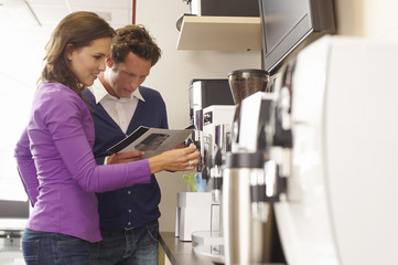 A young couple looking at a coffee maker brochure in an electrical shop