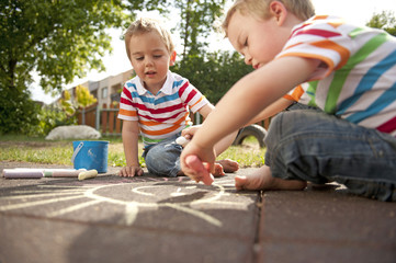 Twin brothers drawing in playground with chalks