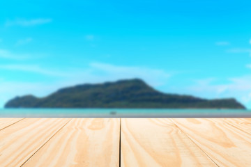 wood table top on blur tropical sea and island beach background. for display and montage products