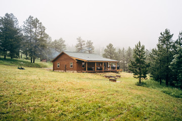Log cabin with porch by forest
