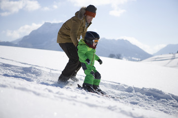 Father and boy learning to ski