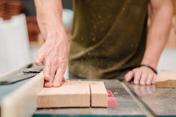 Carpenter cutting wood on table saw
