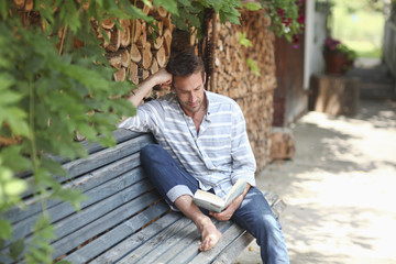Man reading book on bench