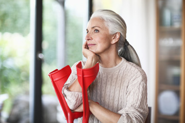 Mature woman leaning on red crutches, looking away