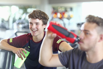 Teenage boys drinking from bottle in gym