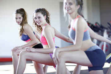 Portrait of teenage girls stretching in gym