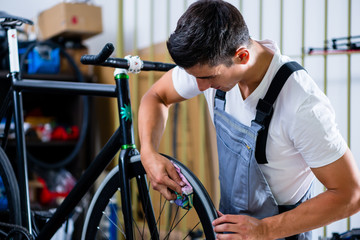 Mann als Fahrradmechaniker arbeitet an Fahrrad