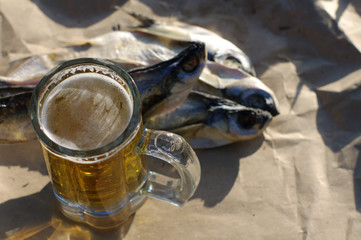 Glass of beer and salty fish (Pelecus cultratus) on gray crumpled paper, top view. Beer and snack to beer.