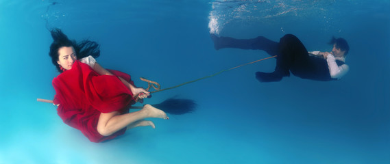 The witch flying on a broom under the water and drags man to las