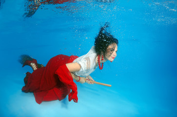A young woman with big hair posing in a pool underwater