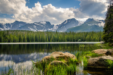 Landscape of a trees and mountains reflected in a lake.