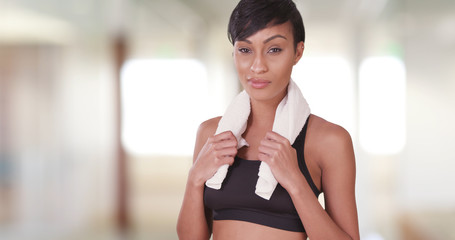 Athletic woman in gym after workout with towel around her neck