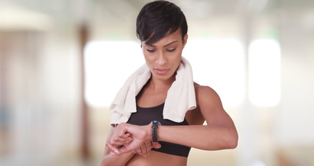 Black woman in gym using smart watch to check heart rate