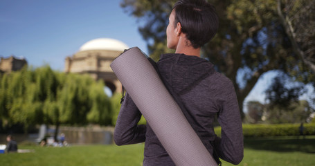 Healthy black woman with yoga mat in park waiting for class to s