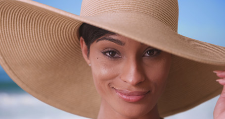 Black woman with big sunhat looking at camera and smiling