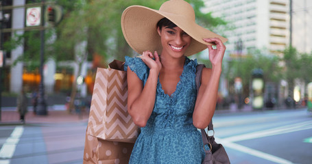 Smiling woman with shopping bags over her shoulder wearing blue