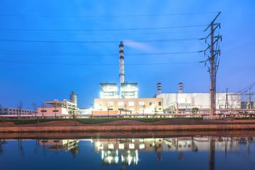 modern factory near river in blue sky at dawn