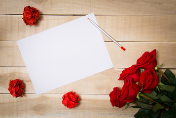blank sheet of paper on the table beside him a bouquet of red ro