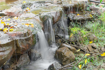 Deep forest Waterfall small, Beautiful  of waterfalls with soft flowing water and large colored rocks.