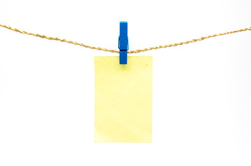 Blue clothespins and yellow note paper hanging on rope isolated white background