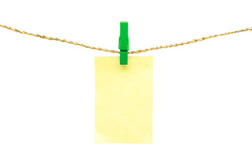Blue clothespins and yellow note paper hanging on rope isolated