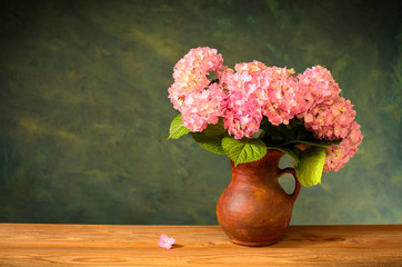Pink hydrangea in a ceramic vase on the voden table
