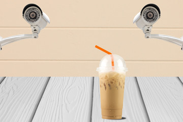 CCTV system security on wall with iced coffee on wood floor.
