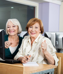 Happy Senior Women At Computer Desk In Classroom