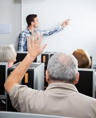 Senior Man Raising Hand In Computer Class