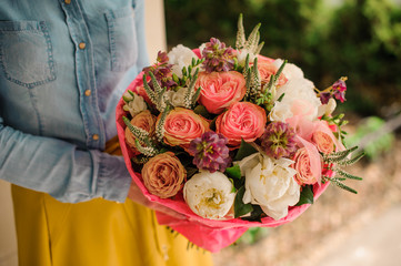 girl holding Bouquet of the different mixed orange and white flowers