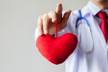 Doctor showing compassion and support holding red heart