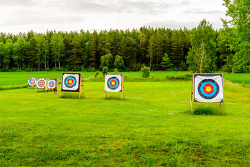 Outdoor archery targets on grass field surrounded by forest in the summer evening.