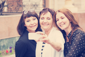 Three mature women friends doing selfie on a mobile phone